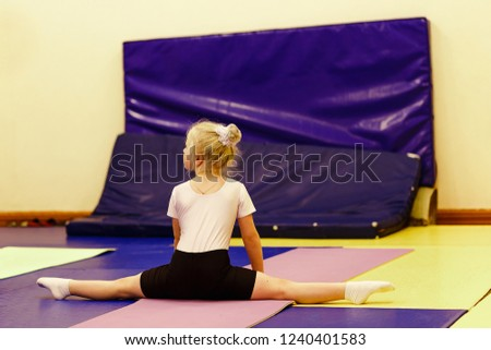 Stock Photo six-year-old blonde girl in a white t-shirt sitting on a cross twine in the gym, back to the camera. gymnastics and children