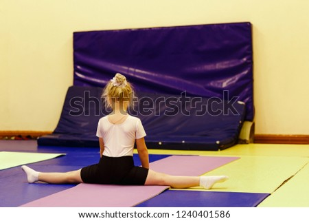 Stock Photo six-year-old blonde girl in a white t-shirt sitting on a cross twine in the gym, back to the camera. children's acrobatics