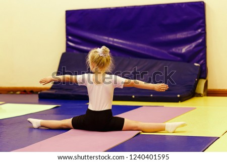 Stock Photo six-year-old blonde girl in a white t-shirt sitting on a cross twine in the gym, back to the camera