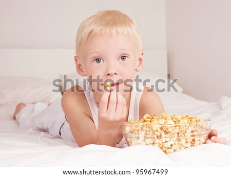 six year old boy boy eating popcorn in bed at home