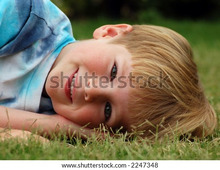Six year old boy lying down in the grass.