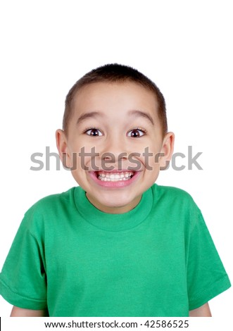 six-year-old boy making a silly face, with a big toothy smile, isolated on white background