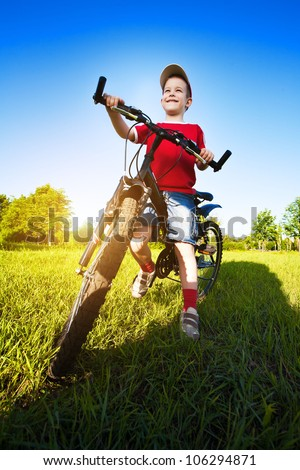 Six  year old boy on a bike on a beautiful sunny meadow
