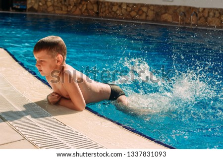 six-year-old boy swimming in the outdoor pool at the hotel in summer #1337831093