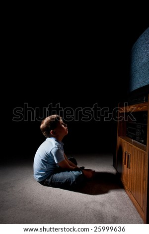 Six year old boy watching static on television in the dark