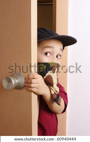 Six-year-old boy wearing a camouflage-colored bandanna mask, sneaking in through a door