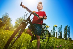 Six year old boy with his bike standing against the blue sky