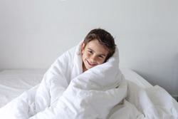 six year old boy wrapped himself in a white blanket while sitting on the bed and smiling