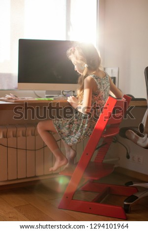 Six-year-old girl makes a picture of crystals, handmade owl. She is sitting at the desk on a wooden red chair. Craft idea for kids. How to spend time with the child.