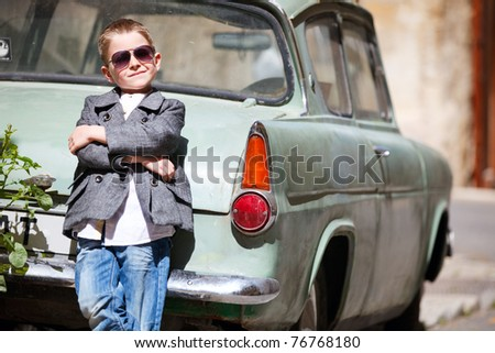 Six years old boy outdoors in citystandimg near old car