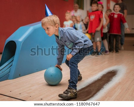 Six years old boy playing bowling during birthday party. - Shutterstock ID 1180967647