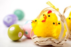 Six yellow chickens in straw baskets. Easter decoration. Painted easter eggs in background. Studio photo isolated on white background. Selective focus.