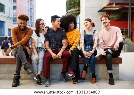 Six young adult friends sitting in a row on a bench in the street looking at each other, full length Foto stock ©
