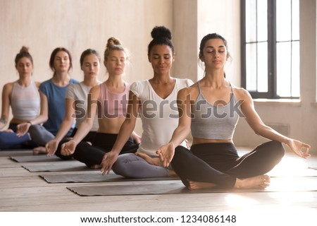 Six young multi-ethnic diverse attractive women sitting in row in lotus position or Padmasana meditate practising yoga together during session. Group training healthy lifestyle and wellness concept