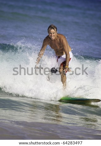 sixty-four year old man surfing in hawaii - stock photo