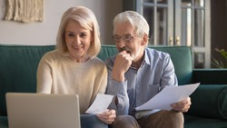 Sixty years old couple sit on couch in living room spouses feels satisfied check online banking bank account balance, paying utility bills, mature family planning budget good news enough money concept