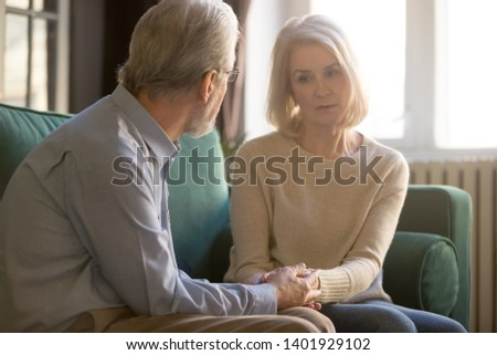 Sixty years old spouses sitting on couch, loving elderly husband comforting sad frustrated wife, hoary couple holds hands man demonstrates love, care and empathy, showing beloved woman support concept