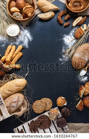 Siyah kara tahtada rustik ekmek rulosu veya Fransız baget, buğday ve un. Kırsal mutfak veya fırın - boş metin alanı arka plan Fresh bakery food rustic crusty loaves of bread and buns on black stone Stok fotoğraf ©