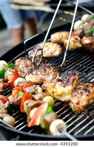 Sizzling chicken and sausages with lamb kebabs and vegetables on hot barbecue grill