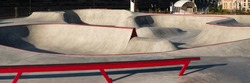 Skate park with concrete bowl, rail and pump track
