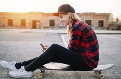 Skateboard girl using listening to music with smartphone