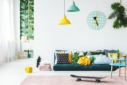 Skateboard on pink rug in colorful kid's room interior with pillows on green mattress under lamps