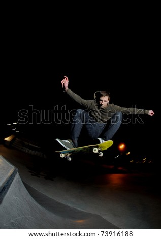 skateboarder blasting a big ollie at night at the local skatepark.