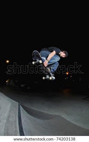 skateboarder blasting a big ollie at night at the local skatepark.