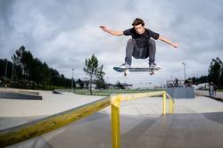 Skateboarder doing a ollie over the rail at the skate park.