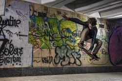 Skateboarder doing a skateboard trick against graffiti wall