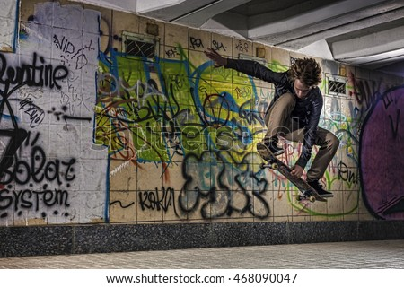Skateboarder doing a skateboard trick against graffiti wall
