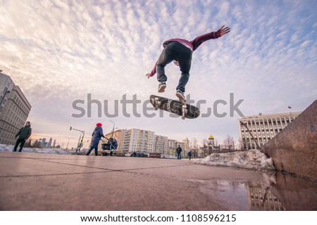 Skateboarder doing tricks at the Kaluzhskaya square near the Gorky park, city centre. March 26, 2018, Moscow, Russia. #1108596215