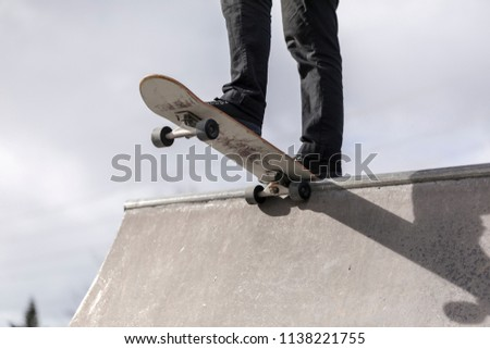 Skateboarder dropping in, a mature male skateboarder preparing to drop in at a skatepark