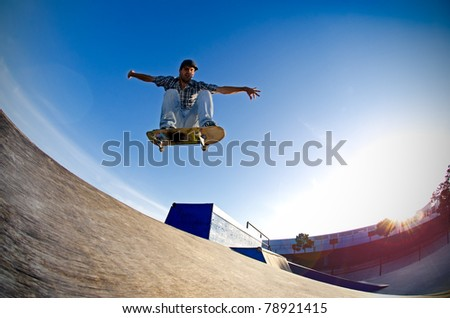 Skateboarder flying over a ramp on sunset at the local skate park.