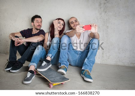 Skateboarder friends taking photo portrait with mobile phone against concrete wall.
