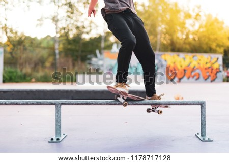 Skateboarder is doing a smith grind trick on a rail in skatepark