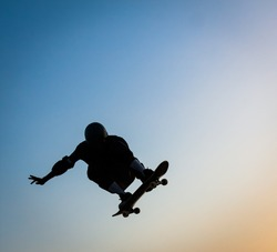 skateboarder jumping with blue sky in background