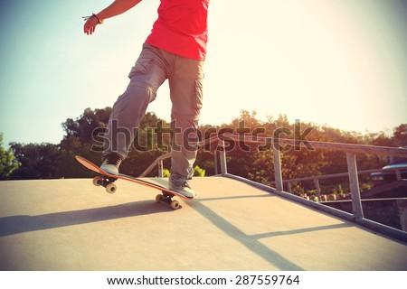 skateboarder legs riding skateboard at skatepark ramp,vintage effect