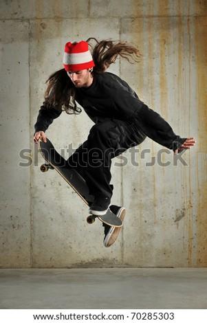 Skateboarder performing jump over grunge building
