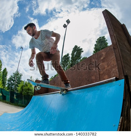 Skateboarder rolling down from halfpipe at skatepark.