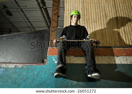 Skateboarder sitting on ramp holding his board