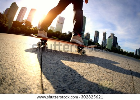 skateboarder skateboarding at sunrise city  #302825621
