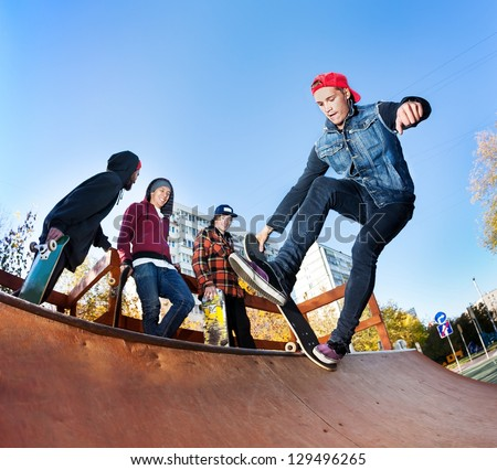 Skateboarder with friends in skatepark jumping in the halfpipe