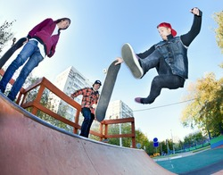 Skateboarder with friends in the skatepark jumping in the halfpipe. Shooting fisheye lens optics