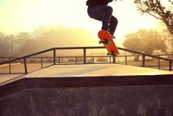 skateboarding legs at sunrise skatepark