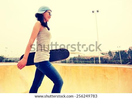 skateboarding woman walking at skatepark  #256249783