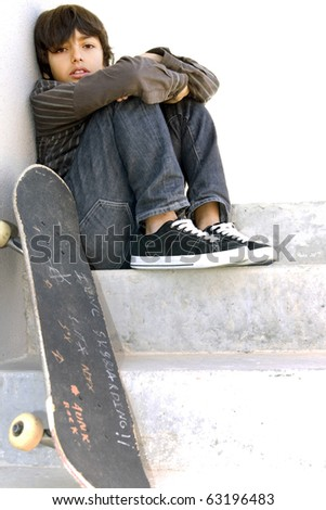 Skater boy: Boy looking bored is sitting on concrete steps with his skateboard. White copy-space