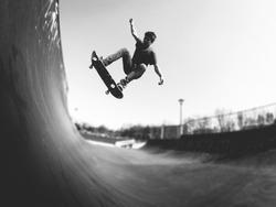 Skater boy making frontside ollie trick on the ramp