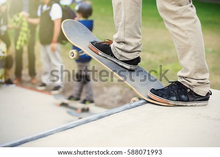 Skater boy stands on big ramp coping in skatepark.Skateboarder guy rides skate board in open outdoor concrete park.Cool extreme summer sports for youth.Focus on sneakers