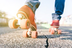 Skater close up in action. Roller skates shoes with sun beam in the background.